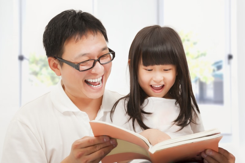 Kids Dentist Singapore - a father teaching her daughter about oral care and preventing tooth decay