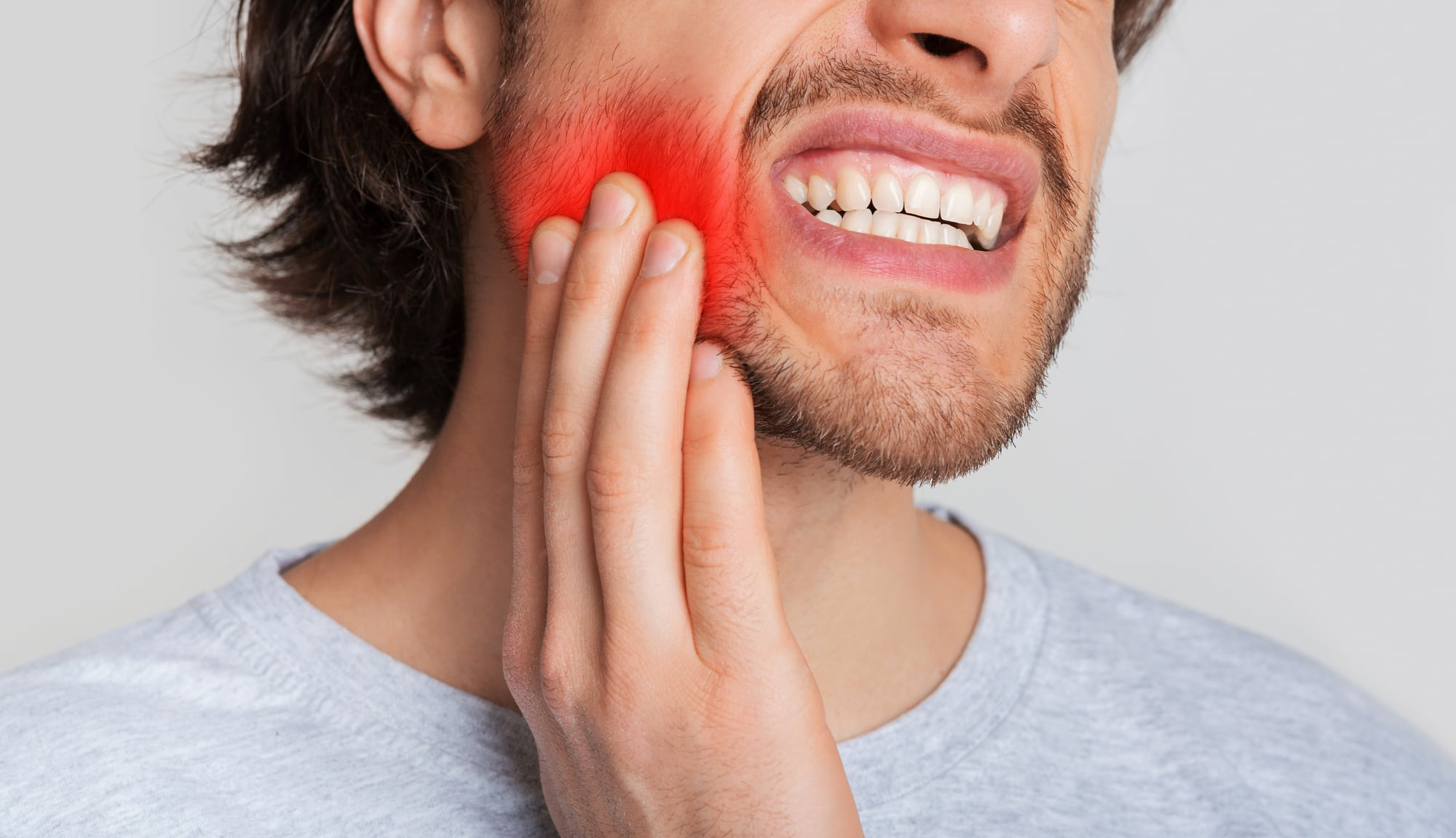 Tooth and gum inflammation. Guy suffers from pain in his mouth and presses hand to red sore spot